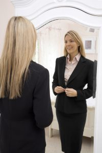 woman-buttoning-her-blazer-while-looking-at-the-mirror